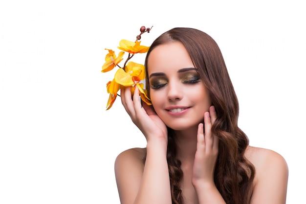 Mujer hermosa con la flor de la orquídea aislada en blanco