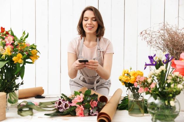 Mujer hermosa floreria en delantal trabajando en flor y tomando fotos con el teléfono móvil del ramo en la mesa