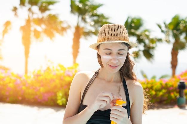 Mujer hermosa frotis cara protector solar en la playa para protegerse del sol
