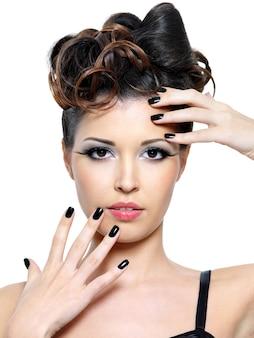Mujer hermosa glamour con peinado moderno y uñas negras. maquillaje de ojos de moda