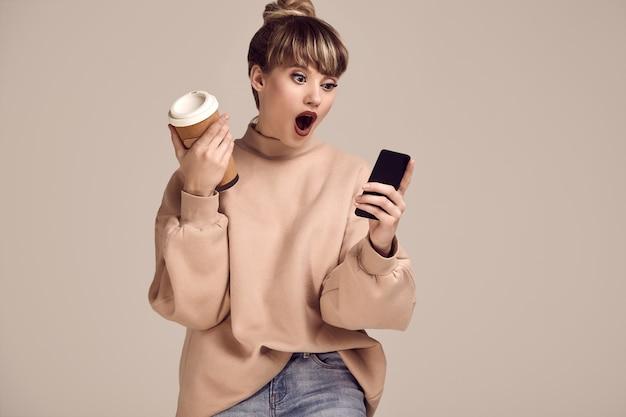 Mujer hermosa glamour rubia hipster con taza de café y teléfono