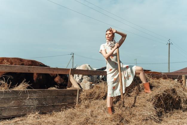 Una mujer hermosa en una granja alimenta el ganado con heno.