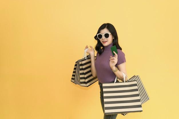 La mujer hermosa está haciendo compras en la alameda. mujer que lleva los vidrios y el sombrero que llevan a cabo la moda del panier en grandes almacenes.
