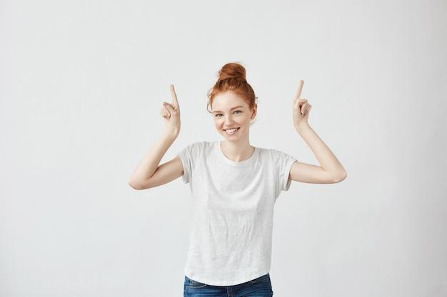 Mujer hermosa del jengibre con las pecas que sonríen señalando los dedos para arriba.