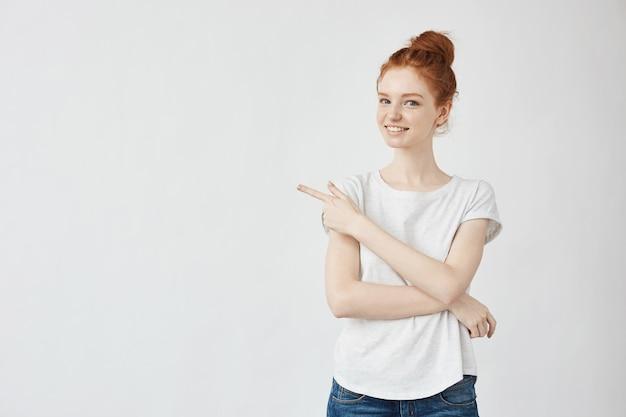 Mujer hermosa del jengibre que sonríe señalando el dedo en lado.