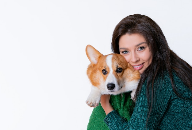 Mujer hermosa joven abrazando corgi perro