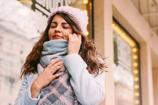 Mujer hermosa joven en abrigo y sombrero a finales de otoño o invierno o