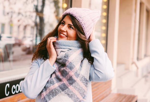 Mujer hermosa joven en abrigo y sombrero a finales de otoño o principios de invierno en la calle de la ciudad disfrutando de la vida