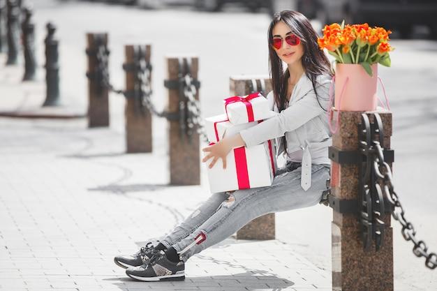 Mujer hermosa joven al aire libre en primavera. chica atractiva cerca retrato. señora con regalos, presenta cajas. mujer con flores. mujer alegre celebración de tulipanes.