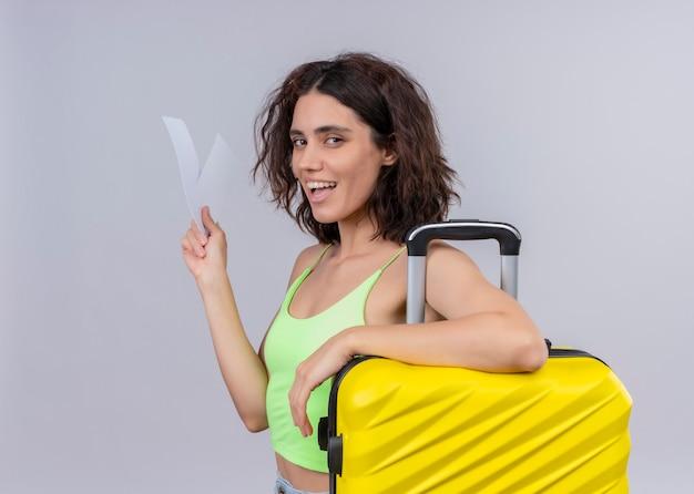 Mujer hermosa joven alegre del viajero que sostiene los billetes de avión y la maleta en la pared blanca aislada