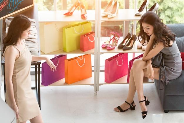 Mujer hermosa joven y amistad que gozan en compras en la tienda.