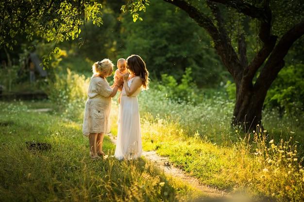 Mujer hermosa joven y anciana juegan con un niño al aire libre
