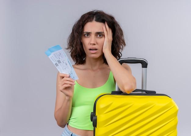 Mujer hermosa joven ansiosa del viajero que sostiene los billetes de avión y la maleta en la pared blanca aislada