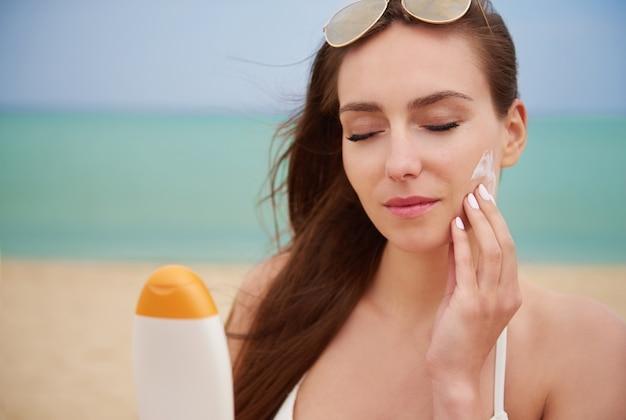 Mujer hermosa joven aplicando crema solar en la playa