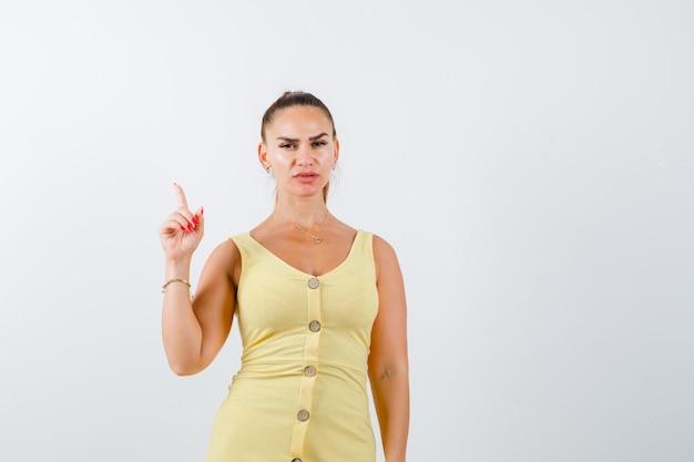 Mujer hermosa joven apuntando hacia arriba en el vestido y mirando triste. vista frontal.
