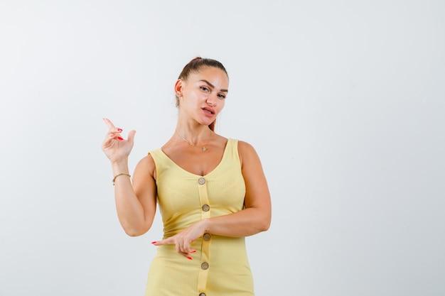 Mujer hermosa joven apuntando a la esquina superior izquierda en vestido y mirando triste. vista frontal.