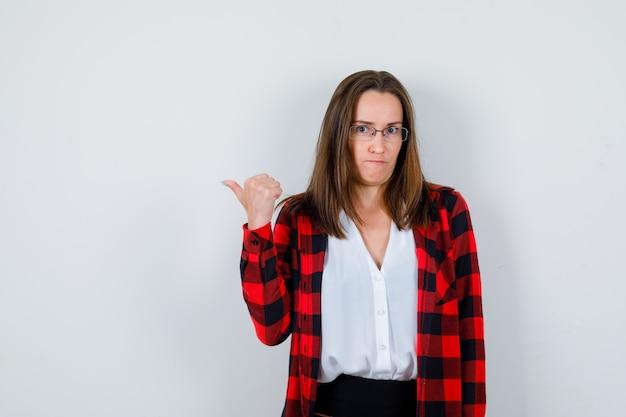 Mujer hermosa joven apuntando hacia la izquierda con el pulgar en ropa casual y mirando pensativo, vista frontal.