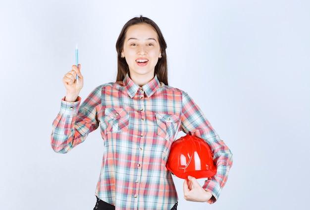 Mujer hermosa joven arquitecto con casco de seguridad con lápiz.