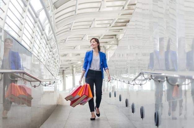 Mujer hermosa joven de asia con bolsas de compras caminando a pie.