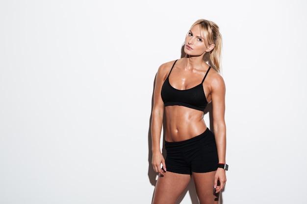 Mujer hermosa joven atleta posando mientras está de pie