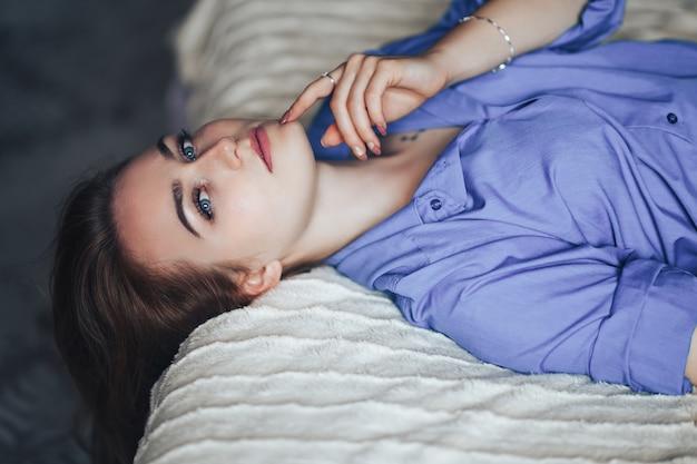 Mujer hermosa joven atractiva con el pelo grande azul del lond de los ojos que miente en cama en casa en camisa azul