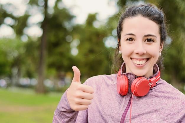 Mujer hermosa joven con auriculares rojos escuchando música
