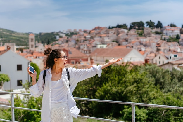 Mujer hermosa joven en un balcón con vistas a un pequeño pueblo en croacia