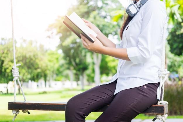 Mujer hermosa joven bastante relajada que lee un libro en el césped del jardín con el sol que brilla.