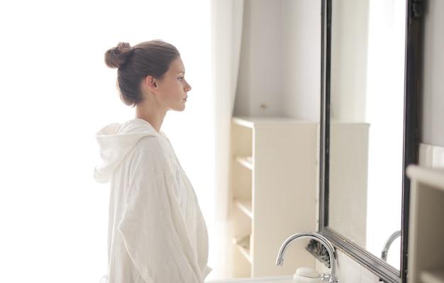 Mujer hermosa joven con una bata y mirando en el espejo en el baño