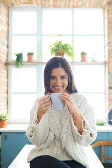 Mujer hermosa joven bebiendo una bebida caliente en la cocina