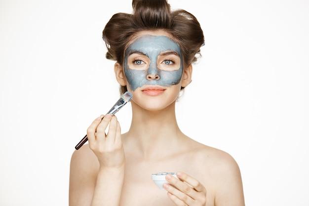 Mujer hermosa joven en bigudís que sonríe cubriendo la cara con mack. tratamiento facial. cosmetología de belleza y spa.