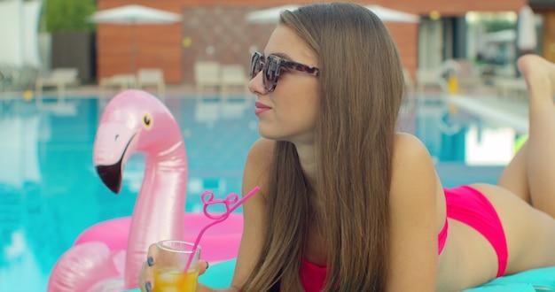 Mujer hermosa joven bikini en verano bebiendo un cóctel