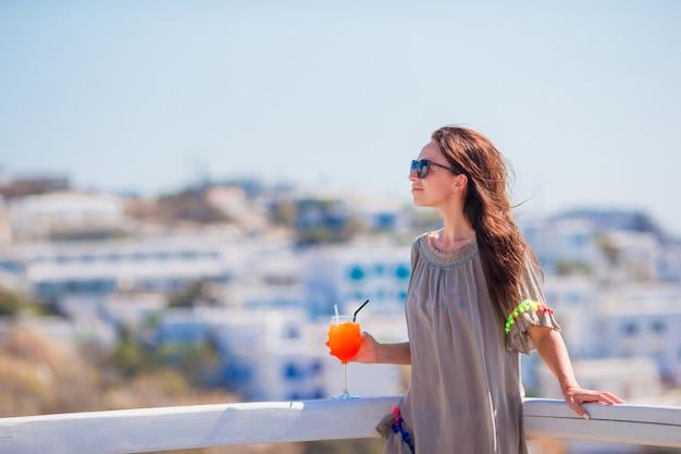 Mujer hermosa joven en café al aire libre con sabroso cóctel. turista feliz disfrutar de vacaciones europeas con una vista increíble de la ciudad vieja en grecia