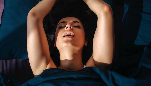 Mujer hermosa joven en cama de la mañana en casa. modelo sensual sensual disfrutando de la intimidad.