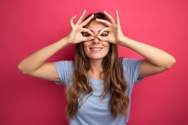 Mujer hermosa joven en camiseta azul mirando a través de los dedos haciendo gesto binocular sonriendo alegremente