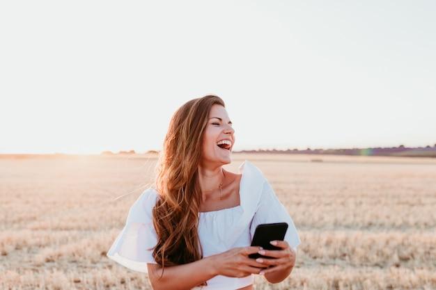 Mujer hermosa joven en campo al atardecer mediante teléfono móvil. concepto de tecnología