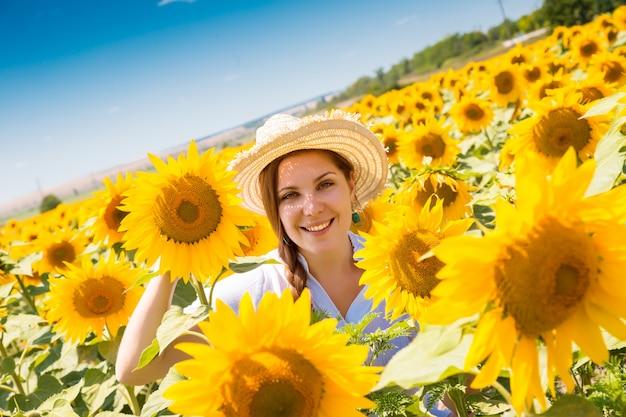 Mujer hermosa joven en campo floreciente del girasol en verano