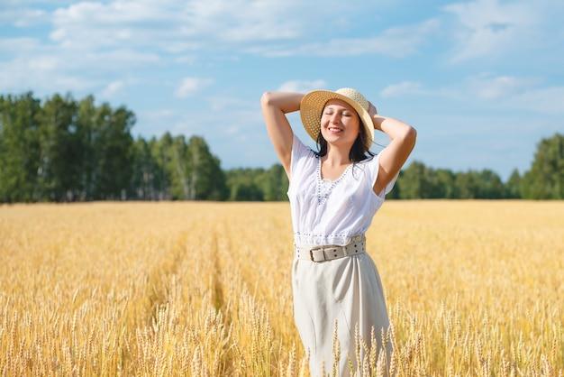 Mujer hermosa joven en campo de trigo dorado