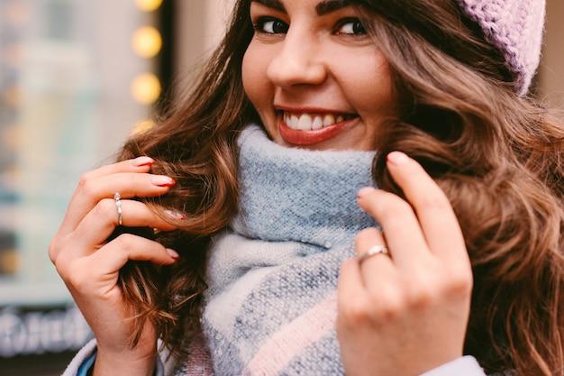 Mujer hermosa joven en capa y sombrero a finales de otoño o invierno en la calle de la ciudad que disfruta de lif