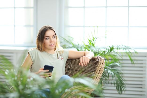 Mujer hermosa joven en casa con plantas
