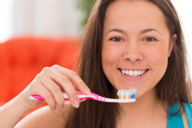Mujer hermosa joven con cepillo de dientes