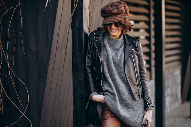 Mujer hermosa joven en chaqueta de cuero fuera de la calle