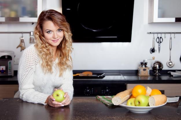 Mujer hermosa joven en la cocina, estilo de vida saludable