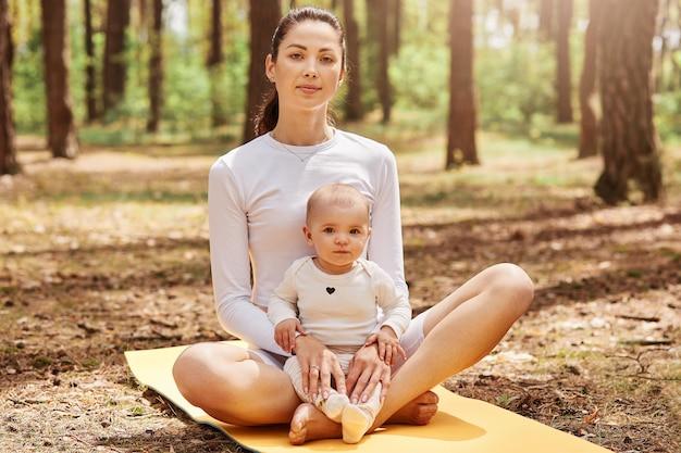 Mujer hermosa joven con cola de caballo sentada en la estera de yoga con la pequeña hija y mirando directamente al frente