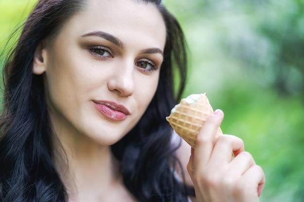 La mujer hermosa joven come el helado en el parque.