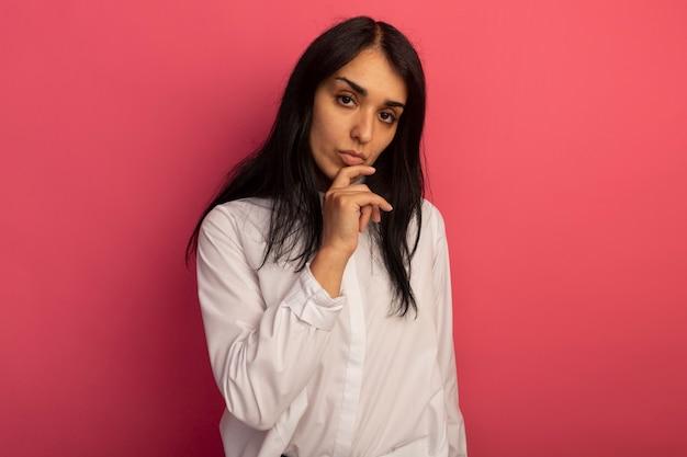 Mujer hermosa joven confiada que lleva la camiseta blanca que pone la mano en la barbilla