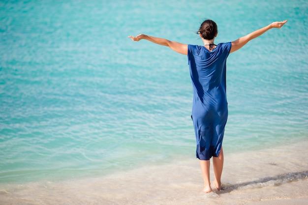 Mujer hermosa joven en la costa tropical. niña feliz relajante en la playa tropical de arena blanca
