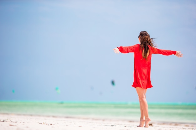Mujer hermosa joven en la costa tropical. vista posterior de la niña en el hermoso vestido de fondo del mar