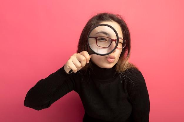 Mujer hermosa joven en un cuello alto negro y gafas mirando al frente a través de la lupa de pie sobre la pared rosa