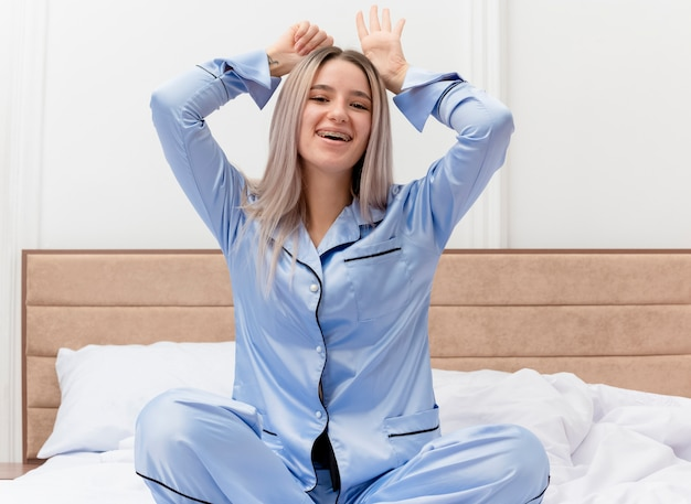 Mujer hermosa joven divertida en pijama azul sentada en la cama feliz y alegre imitando orejas de conejo sonriendo en el interior del dormitorio sobre fondo claro